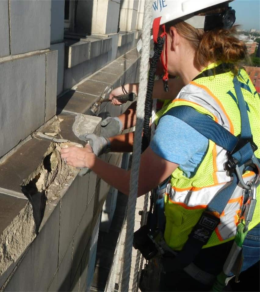 Rachel Will of WJE gets up close to inspect structural damage on the building. Photo courtesy WJE